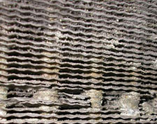 A close view of corroded cooling fins on an indoor evaporator coil